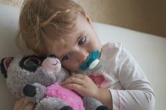 Enfant de portrait de Clouse-up petit s'asseyant sur le lit dans la chambre étreignant un lémur bourré de jouet horizontal Photo libre de droits