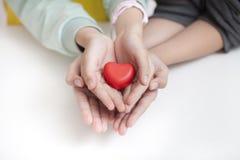 Enfant de remorquage tenant le coeur rouge, plan rapproché Concept d'adoption photographie stock