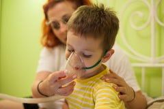 Enfant de soin de mère avec l'inhalation d'aérosols Photos stock