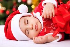Enfant de sommeil Santa de bébé tenant des cadeaux Photo libre de droits