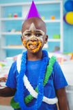 Enfant de sourire avec le glaçage sur son visage photos stock