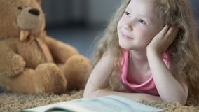 Enfant de sourire brillant avec bonheur et semblant rêveur, se trouvant sur le plancher dans la chambre banque de vidéos