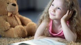 Enfant de sourire brillant avec bonheur et semblant r?veur, se trouvant sur le plancher avec le livre photos stock