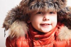 Enfant de sourire dans le capot de fourrure et le garçon orange de l'hiver jacket.fashion Photographie stock