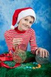 Enfant de sourire dans le chapeau de Santa sur le fond bleu Images stock