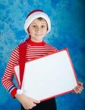 Enfant de sourire dans le chapeau rouge de Santa tenant le conseil blanc Image stock