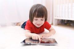 Enfant de sourire dans le T-shirt rouge avec la tablette Photographie stock libre de droits