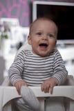 Enfant de sourire drôle dans la chaise de bébé Photos libres de droits