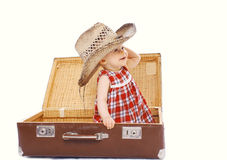 Enfant de sourire heureux dans le chapeau d'été de paille se reposant sur la valise Image stock