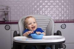 Enfant de sourire heureux dans une chaise de bébé Image libre de droits