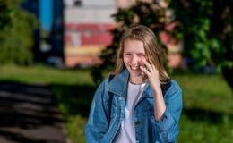 Enfant de sourire heureux En parc d'été en nature L'écolière de fille appelle par le téléphone Émotions de joie et de plaisir Images stock