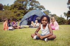 Enfant de sourire posant sur l'herbe pendant un jour ensoleillé avec d'autres enfants Image libre de droits