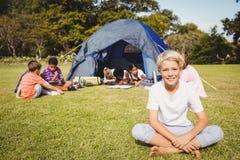 Enfant de sourire posant sur l'herbe pendant un jour ensoleillé avec d'autres enfants Image stock