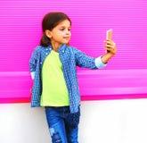 Enfant de sourire prenant le selfie par le smartphone dans la ville sur le mur coloré images stock