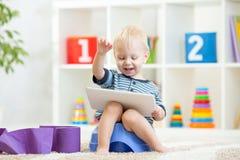 Enfant de sourire s'asseyant sur le pot de chambre avec du papier hygiénique Image libre de droits