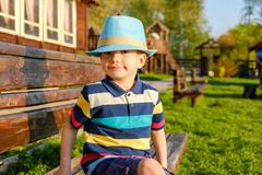 Enfant de sourire s'asseyant sur un banc de parc avec le pré vert sur le fond Photo stock