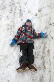 Enfant de sourire se trouvant sur la neige photo libre de droits
