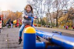 Enfant de sourire sur la bascule sur le terrain de jeu en parc images libres de droits