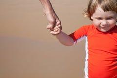Enfant de sourire tenant la main de la femme à la plage Photos libres de droits