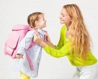 Enfant de soutien de maman pour utiliser un sac à dos Photo libre de droits