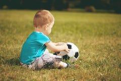 Enfant de sports Garçon jouant au football Bébé avec la boule sur le champ de sports Photos libres de droits