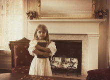 Enfant de vintage tenant le livre d'école dans la maison Image stock