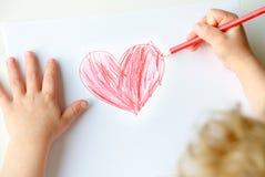 Enfant dessinant un coeur Photographie stock libre de droits