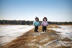 Enfant deux en dehors des vêtements chauds d'hiver de champ photographie stock