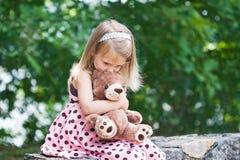 Enfant donnant à nounours une étreinte et un baiser. Image stock