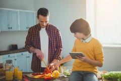 Enfant donnant des signes de papa dans la cuisine Photo stock