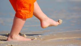 Enfant donnant un coup de pied le sable Image libre de droits