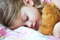 Enfant dormant avec l'ours de nounours Photos stock
