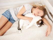 Enfant dormant avec le chat Images stock