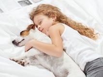 Enfant dormant avec le chien sur le lit Image libre de droits
