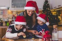 Enfant doux d'enfant en bas âge et son frère plus âgé, garçons, maman de aide préparant des biscuits de Noël à la maison images libres de droits