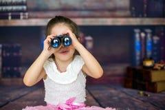 Enfant doux, fille, jouant avec des jumelles Image libre de droits