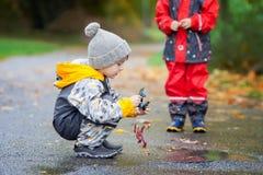 Enfant doux, garçon, jouant en parc un jour pluvieux Images stock
