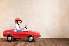 Enfant drôle conduisant la voiture de jouet à la maison photos stock