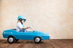 Enfant drôle conduisant la voiture de jouet à la maison photo stock