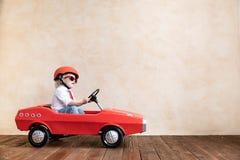 Enfant drôle conduisant la voiture de jouet à la maison images libres de droits