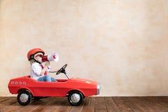 Enfant drôle conduisant la voiture de jouet à la maison image stock