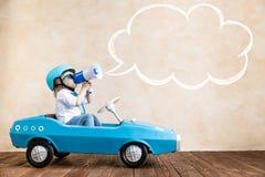 Enfant drôle conduisant la voiture de jouet à la maison photographie stock libre de droits