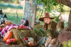 Enfant drôle d'enfant de fille dans le jeu de costume de vert de Halloween extérieur avec les potirons fantasmagoriques de cric a images stock