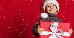 Enfant drôle de sourire dans le chapeau rouge de Santa jugeant le cadeau de Noël disponible Concept de Noël photos libres de droits