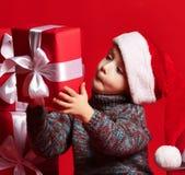Enfant drôle de sourire dans le chapeau rouge de Santa jugeant le cadeau de Noël disponible Concept de Noël photo stock