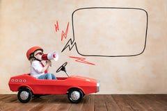 Enfant dr?le conduisant la voiture de jouet ? la maison photos stock