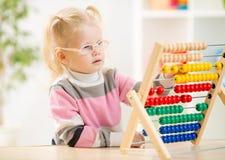 Enfant drôle dans les eyeglases comptant utilisant l'abaque Photographie stock libre de droits