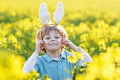 Enfant drôle de 3 ans avec des oreilles de lapin de Pâques, célébrant Pâques Image libre de droits