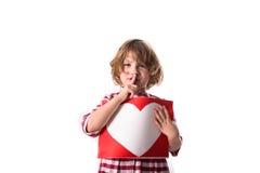 Enfant drôle de fille dans la robe rouge de plaid avec une feuille avec un coeur, Co Photo stock