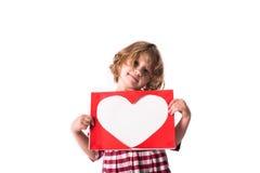 Enfant drôle de fille dans la robe rouge de plaid avec une feuille avec un coeur, Co Images stock